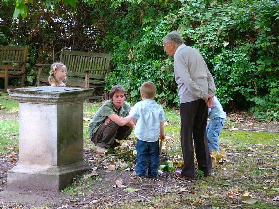 Three generations examining the fox hole in the garden